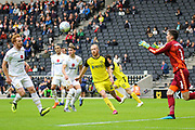 Burton Albion forward Liam Boyce challenges for the ball as Milton Keynes Dons goalkeeper Lee Nicholls makes a save during the EFL Sky Bet League 1 match between Milton Keynes Dons and Burton Albion at stadium:mk, Milton Keynes, England on 5 October 2019.