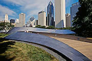 Vsiitors walk on the BP bridge with view of the city skyline at Millenium Park, Chicago, Illinois