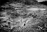 Migrant Brazilian men of unknown visa status (many are known to over stay their Suriname visas) mining for gold with high power water hoses deep on Maroon territory in the interior of the Amazon forest near Bensdorp, Suriname.  The gold miners snake their way up watersheds from the Marowijne River, blasting away organic topsoil to get at the gold rich sediment below.