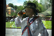 Thaxted Morris Weekend 3-4 June 2017<br />A meeting of member clubs of the Morris Ring celebrating the 90th anniversary of the founding of the Thaxted Morris Dancing side or team in Thaxted, North West Essex, England UK. <br />A member of the side from Silkeborg in Denmark drinks his beer while other dancers reflected in bus shelter at Finchingfield Essex.<br />Hundred of Morris dancers from the UK and this year the Silkeborg side from Denmark spend most of Saturday dance outside pubs in nearby villages where much beer is consumed. In the late afternoon all the sides congregate in Thaxted where massed dancing is perfomed along Town Street. As darkness falls across Thaxted the spell binding Abbots Bromley Horn Dance is performed to the sound of a solo violin in the dark.