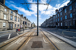 Edinburgh, Scotland, UK. 18 April 2020. Views of empty streets and members of the public outside on another Saturday during the coronavirus lockdown in Edinburgh. York Place on tram lines is empty. Iain Masterton/Alamy Live News