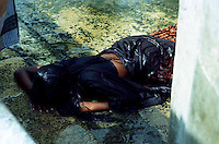 TAMIL NADU, MARCH 1994.A young woman in a state of surrender is lying on the ground after being forcefully cleansed by the 'holy water'. Locals believe that her body is possessed by evil spirits and faith is said to be the only remedy.