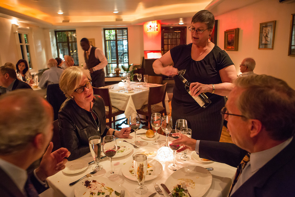 New York, NY - 27 May 2014. General manager and wine enthusiast Tina Vaughn serving wne to a table of guests at The Simone.