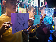 "06 JULY 2015 - BANGKOK, THAILAND: Women stand in support of 14 Thai university students arrested two weeks ago for violating orders banning political assembly in Thailand. More than 100 people gathered at Thammasat University in Bangkok Monday to show support for the students. They face criminal trial in military courts. The students' supporters are putting up ""Post It"" notes around Bangkok and college campuses up country calling for the students' release.      PHOTO BY JACK KURTZ"