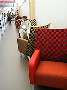 Man at the library sitting in a colorful chair.