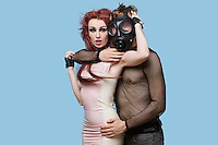 Portrait of young man wearing gas mask embraces funky woman over blue background