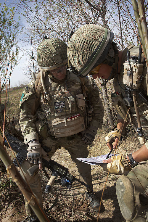 British soldiers of 3PARA discus route and tactics whilst on a foot patrol in Nad Ali, Hemand Province, Afghanistan on the 11th of March 2011.