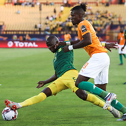 24 June 2019, Egypt, Cairo: Ivory coast's Wilfried Zaha and South Africa's Thamsanqa Mkhize battle for the ball during the 2019 Africa Cup of Nations Group D soccer match between South Africa and Ivory coast at Al-Salam Stadium. Photo : PictureAlliance / Icon Sport