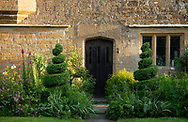 Spirals of box topiary next to the front door at Lower Severalls Farmhouse,  Crewkerne, Somerset, UK