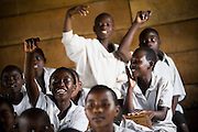 Children raise their hands to answer their teacher's question at the Mboga primary school in the town of Kibati, on the outskirts of Goma, Eastern Democratic Republic of Congo on Friday December 12, 2008. Classes started again on Dec 1 after the school was occupied during 8 weeks by IDPs fleeing fighting.