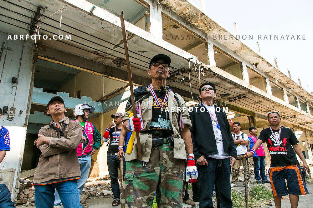 A group of anti-government protestors in an abandoned apartment complex look out for a suspect whom threw an explosive device injuring 30 people during an anti-government street rally on January 17, 2014 in Bangkok, Thailand