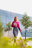 Portrait of young attractive businesswoman walking while holding digital tablet