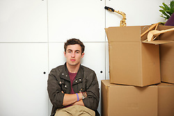 Man Sitting with Arms Crossed by Cardboard Boxes