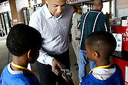 Newark Mayor Cory Booker gives two young boys money to buy  hot dogs at a Newark Bears game on June 13, 2006,