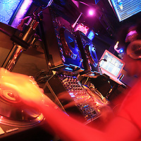 DJ spinning at modern DJ booth at nightclub - Turntable.