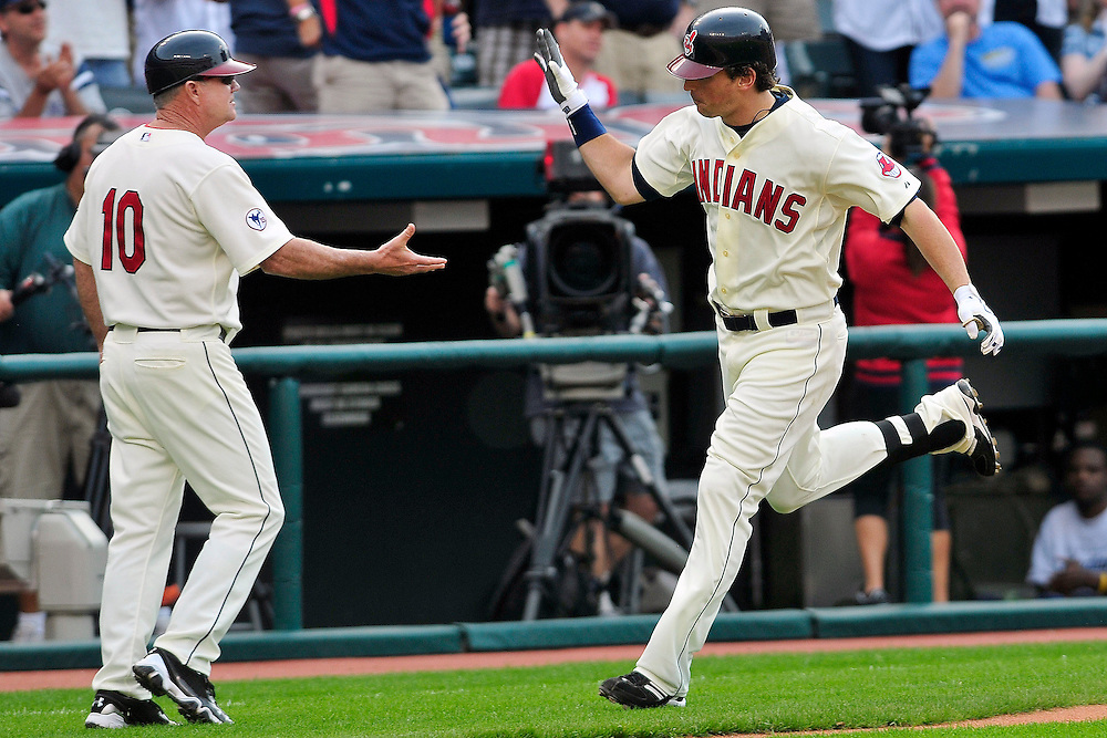 May 21, 2011; Cleveland, OH, USA; Cleveland Indians third base coach Steve Smith (10) congratulates right fielder Travis Buck (28) as he rounds the basses after a two run home run during the seventh inning against the Cincinnati Reds at Progressive Field. Mandatory Credit: Jason Miller-US PRESSWIRE