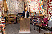 Salesman with traditional Turkish carpet rug in The Grand Bazaar, Kapalicarsi, great market, Beyazi, Istanbul, Republic of Turkey