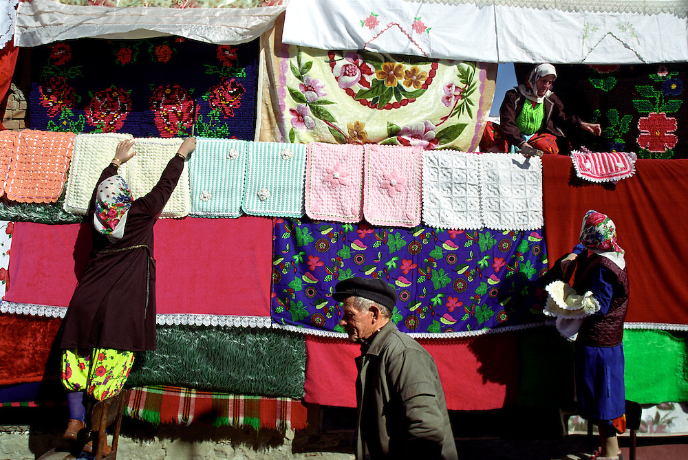 Women from Fatme's family arrange all the blankets, carpets and cushion covers on the wooden pillars outside Fatme's house as a local man walks by. All the cushion covers are handmade by Fatme and her mother.