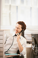 Mid-adult male office worker sitting in cubicle talking on phone