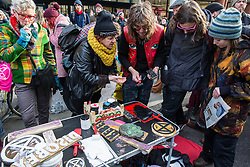 London, UK. 9th February, 2019. Activists from Extinction Rebellion offer a printing service to customise clothes during a 'Saturday street party' in Kingsland Road in Dalston intended as a means of engagement around climate change and environmental issues with the local community.