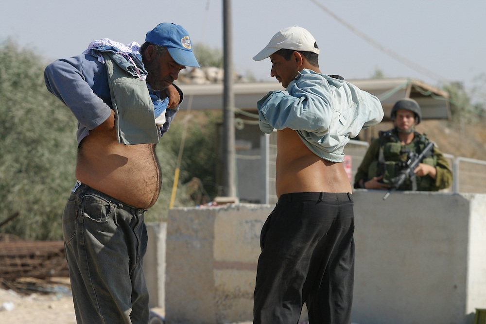 Palestinian workers  checked for weapons by Israeli soldiers before they go into  Jewish settlement   Gush Katif     Gaza Strip,