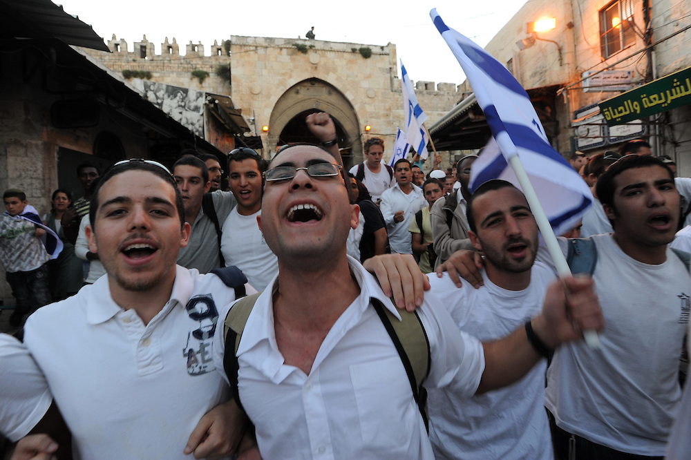 JERUSALEM, ISRAEL - MAY 12, 2010: Israeli youth wave Israeli flags and sing in the Muslim Quarter of Jerusalem's Old city during a march celebrating Jerusalem Day, Thursday, May 12, 2010. Thousands took part in Jerusalem Day celebrations in the capital, marked the 43nd anniversary of its capture of Arab east Jerusalem in the Six Day War of 1967. Photo by GILI YAARI/NEWS-PICTURES