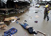 A Liberian government gunman walks past the corpses of Liberians killed for looting in the embattled Westpoint district between the 'Old' and 'New' bridges, Monrovia 03 August 2003.  Battles between LURD rebel forces waged on today concentrated at the 'New Bridge'. Peacekeepers are due to arrive in the country tomorrow.<br /> EPA PHOTO/NIC BOTHMA
