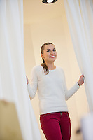 Happy woman in dressing room opening curtains