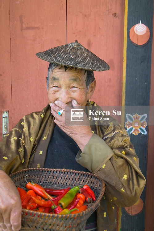 Portrait of a farmer carrying basket of red peppers, Gangtey, Bhutan