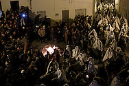 """Horsemen march next to a bonfire during the """"La Encamisa"""" Festival on December 7,  2014 in Torrejoncillo, Extremadura region, Spain. """"La Encamisa"""" is an ancient festival in honor of Immaculate Conception. Hundreds of horsemen wearing a white sheet gather outside the church in the main square. The procession starts when a banner with the image of Immaculate Conception is delivered to the horse rider steward and people cheer and shoot blanks. There are bonfires along the way where people gather to chat, eat traditional sweets and drink local wine. The origin of this tradition is unknown but it is believed the festival comes from a military event in which people from Torrejoncillo were involved. The war in Flanders in 1585, the Battle of Pavia or a legend of the siege suffered by city of Coria. (© Pablo Blazquez)"""