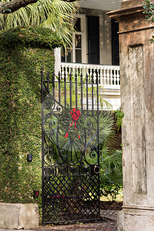 The wrought iron gate of a historic home decorated with a Christmas wreath on Lagare Street in Charleston, SC.