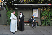 TWICKENHAM LONDON. Religious Pilgrims stand at a bus stop next to the entrance to St Mary's University. The Richmond Coalition Against the State Visit greet Pope Benedict XVI as he visits St Mary's University in Twickenham for a Celebration of Roman Catholic education. The Coalition oppose the Pope's opinions on condom use, abortion, gay rights and education. 17 September 2010. STEPHEN SIMPSON