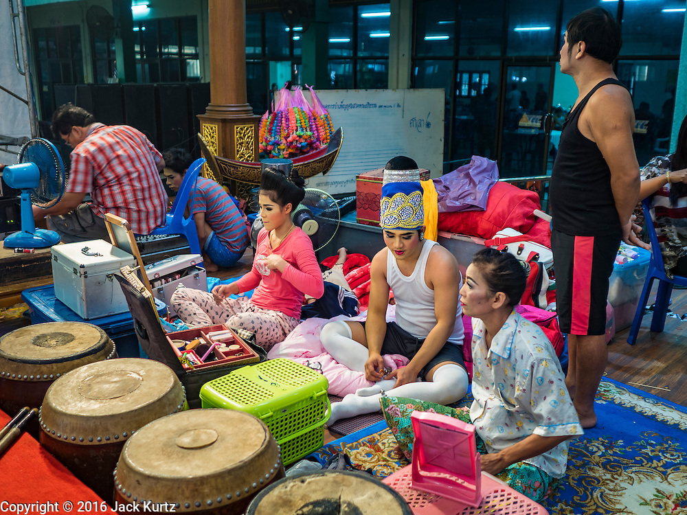 "30 JANUARY 2016 - NONTHABURI, NONTHABURI, THAILAND: Performers backstage before a ""likay"" show at Wat Bua Khwan in Nonthaburi, north of Bangkok. Likay is a form of popular folk theatre that includes exposition, singing and dancing in Thailand. It uses a combination of extravagant costumes and minimally equipped stages. Intentionally vague storylines means performances rely on actors' skills of improvisation. Like better the known Chinese Opera, which it resembles, Likay is performed mostly at temple fairs and privately sponsored events, especially in rural areas. Likay operas are televised and there is a market for bootleg likay videos and live performance of likay is becoming more rare.     PHOTO BY JACK KURTZ"
