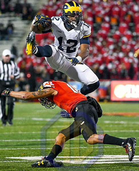 COLLEGE PARK, MD - NOVEMBER 11:  Michigan Wolverines running back Chris Evans (12) leaps over Maryland Terrapins defensive back Josh Woods (10) on a fourth quarter run on November 11, 2017, at Capital One Field at Maryland Stadium in College Park, MD.  The Michigan Wolverines defeated the Maryland Terrapins, 35-10.(Photo by Mark Goldman/Icon Sportswire)