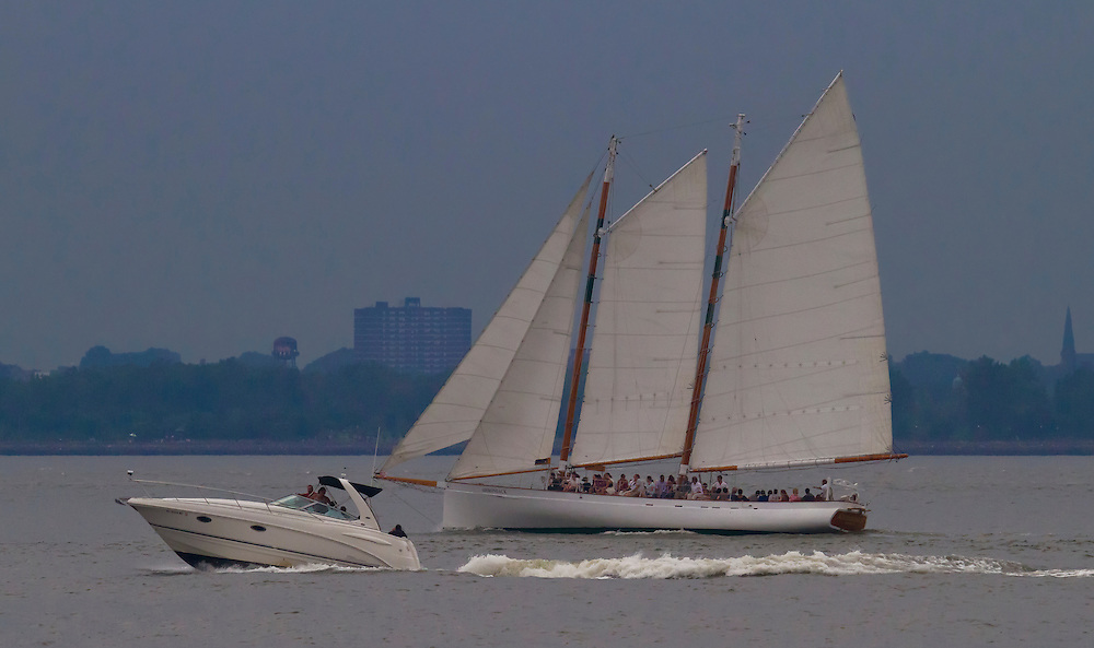 Sail boat being passed by a noisy speed boat in the Hudson River.