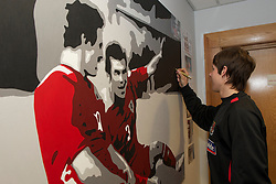 SWANSEA, WALES - Monday, March 1, 2010: Wales' Chris Gunter autographs a painting before training at the Liberty Stadium ahead of the international friendly match against Sweden. (Photo by David Rawcliffe/Propaganda)