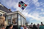 Nederland, Noordpolderzijl, 14-10-2018In het noordelijk kustgebied van Gronongen bevindt zich uitspanning het Zielhoes . De groningse vlag hangt uit, een muzikantenduo zingt liederen in dialect. Hier bevindt zich het kleinste open zeehaventje van Nederland. Een oud sluisje is in de dijk gebouwd en geeft toegang tot het binnenland . Veel dagjesmensen komen hier genieten van het wijdse uitzicht . Noordpolderzijl is onderdeel van de gemeente Eemsmond .Foto: Flip Franssen