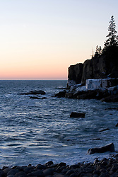A crescent moon hangs above Otter Cliffs at dawn in Maine's Acadia National Park.