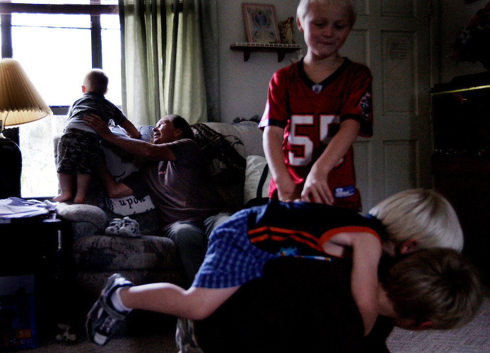 After coming home from school and changing, Katherine Smith's, great grandsons, Caleb Huth, 1, left, Jordan Thompson, 8, top right, Eran Huth, 4, middle right, and Justin Thompson, 9, bottom right, spend all their pent-up energy in the house as Smith, center,  tries to keep anyone from being injured. Smith doesn't tire of the children but she does have a bad back, which on certain days will keep her on the couch. Greg Kahn/Staff