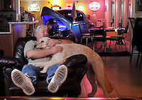 Gordon Robinson hangs with Jack, the  golden doodle, in his 2,300 square foot man cave, which contains three flat screen TVs, three classic cars, a walk-in gun vault, a wet bar and full kitchen among other amenities, in Lakewood, January 25, 2011.(Janet Jensen/Staff photographer)
