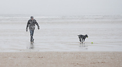 © Licensed to London News Pictures. 14/01/2013..Saltburn beach, Cleveland, England..A man walks his dog through heavy snow on Saltburn Beach as parts of North Yorkshire and East Cleveland saw heavy snow fall today.  ..Photo credit : Ian Forsyth/LNP