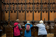 Visitors admire intricate wooden carvings in the choir of St. Laurence's Church, Ludlow, on 11th September 2018, in Ludlow, Shropshire, England UK.