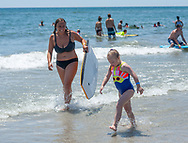 Cape May County Tech Swim Team member Ally Boehm walks with Ella Nichols in the surf during the 11th annual 21 Down Beach Day Monday, July 15, 2019 at Schellenger Street beach in Wildwood, New Jersey. Every summer, the Wildwood Beach Patrol opens Lincoln Ave Beach for kids with down syndrome and their families for 21 Down Beach Day. Often, kids with down syndrome aren't comfortable in the ocean. Their parents can't just relax and watch them frolic. But on July 15th, the kids swim with seasoned Wildwood lifeguards on soft-top paddle boards. (Photo by William Thomas Cain / CAIN IMAGES)