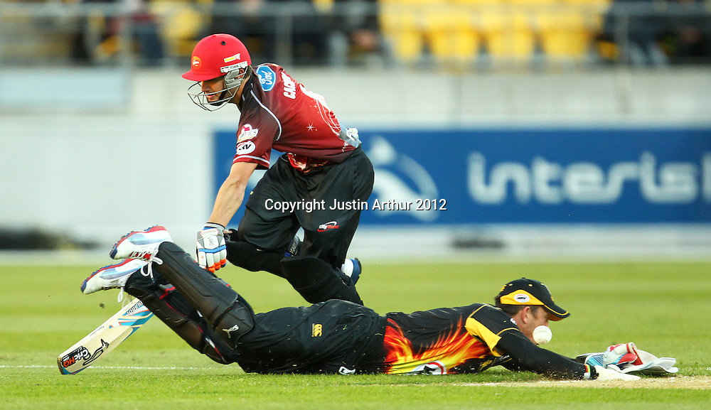 Firebirds' Luke Ronchi miss fields the ball as Wizards' Brad Cachopa makes his ground during the 2012/2013 HRV Cup Twenty20 session. Wellington Firebirds v Canterbury Wizards at Westpac Stadium, Wellington, New Zealand on Friday 9 November 2012. Photo: Justin Arthur / photosport.co.nz