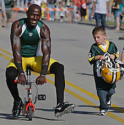 The smile is big but the bike small as Donald Driver gets a ride to Training camp practice held on the new Ray Nitschke Field, Sunday, August, 2, 2009 in Green Bay. Jeffrey Phelps