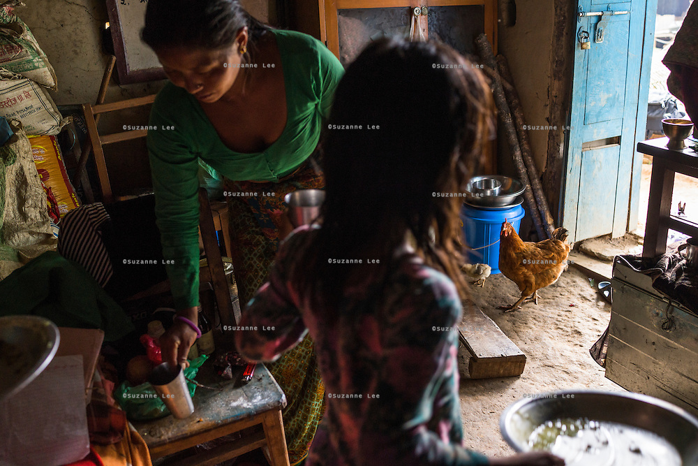 Kalpana Tamang (40), gets her younger daughter Binita (10) ready for school as she finishes her lunch in their temporary shelter in Kavre, Bagmati, Nepal on 30 June 2015.  Kalpana, a widow with 3 children, has been supported by SOS Children's Villages for many years now and had receive the Home-in-a-Box after the earthquake destroyed her house, almost killing her two daughters. She now lives in a temporary shelter, sharing her dwelling with farm animals, and is trying to make ends meet by weaving bamboo baskets to supplement the financial assistance provided by SOS Childrens Villages. The NGO mostly supports her children's welfare and schooling as well as provides her with essential household and schooling items like kitchen utensils and school books and uniforms. Photo by Suzanne Lee for SOS Children's Villages