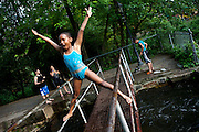 "BETHLEHEM, PA – MAY 27, 2011: Niyanda Magagi, 9, does a stunt over the water at the Lehigh Canal on a Saturday afternoon at Sand Island in Bethlehem, Pennsylvania. Commonly known as ""The Box,"" the water at Sand Island is one of several well known recreational spaces for the burgeoning Latino community in the town of Bethlehem.<br />