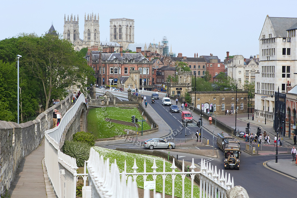 Tourists are walking along York City Wall and Minster, in Yorkshire, England, United Kingdom.
