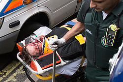 © Licensed to London News Pictures . 11/06/2013 . London , UK . An injured man being wheeled on to an ambulance on Golden Square in Soho , adjacent to Beak Street where police detained dozens of protesters who had occupied an empty police station today (Tuesday 11th June) . Demonstrations in London today (Tuesday 11th June 2013) ahead of Britain hosting the 39th G8 summit on 17th/18th June at the Lough Erne Resort , County Fermanagh , Northern Ireland , next week . Photo credit : Joel Goodman/LNP