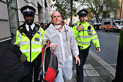 © Licensed to London News Pictures. 08/10/2019. London, UK. Extinction Rebellion activists being arrested after glueing themselves to a staff entrance to Department for Transport in Westminster. Activists have converged on Westminster for a second day, blockading roads in the area and calling on government departments to 'Tell the Truth' about what they are doing to tackle the Emergency. Photo credit: Ben Cawthra/LNP